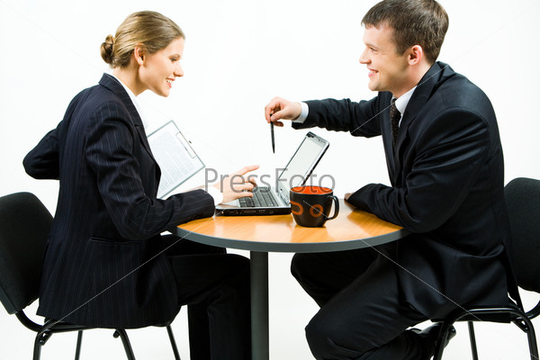 Portrait of two young businesspeople at the table discussing new work