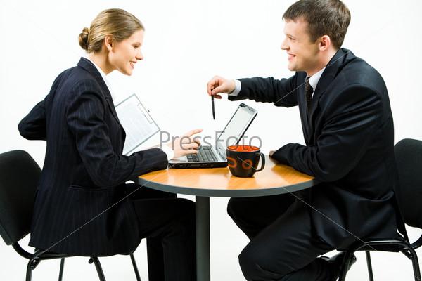 Двое молодых деловых людей обсуждают за столом новую работу
