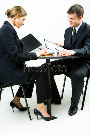 Portrait of woman and man sitting at the table and reading the documents