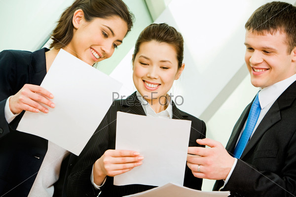 Portrait of three office workers interacting at business meeting