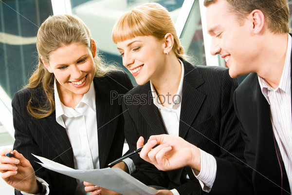 Portrait of three young happy colleagues looking at business plan in the office