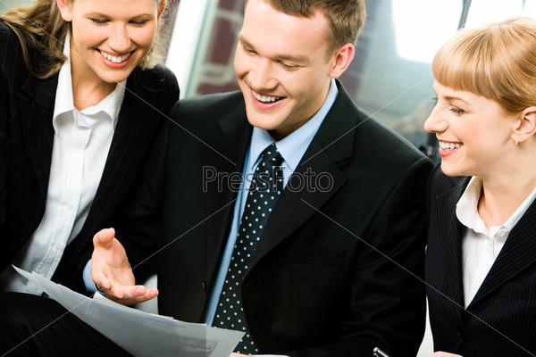 Photo of a young successful businessman between two business ladies