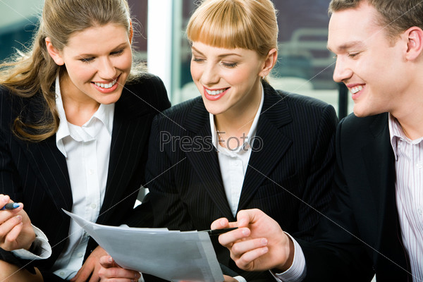 Portrait of three white collar workers looking at the document