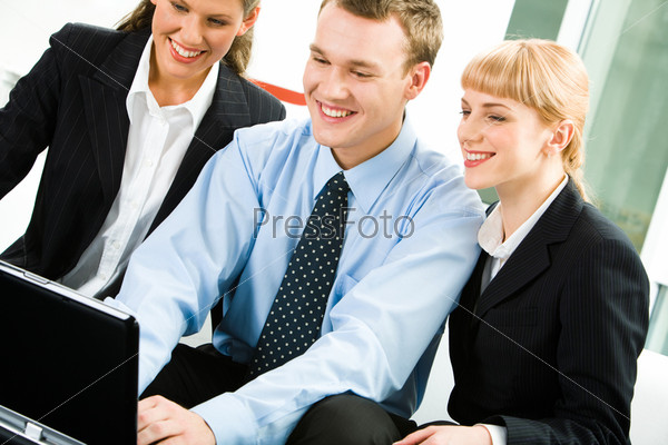 Photo of business partners doing some work and looking at the laptop