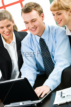 Vertical image of three young specialists looking at monitor of laptop