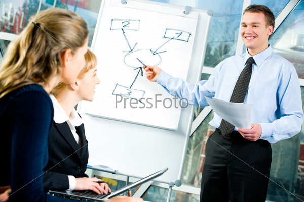 Сonfident man explaining his business strategy pointing to board to coworkers