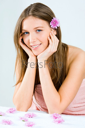 Portrait of young smiling woman in pink towel with the flowers near by