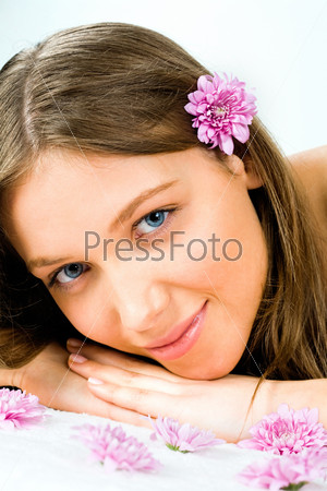 Vertical photo of a young pretty girl lying with her chin on hands and looking at camera