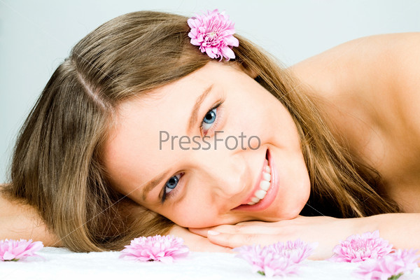 Photo of a young happy woman lying in the spa salon and enjoying herself