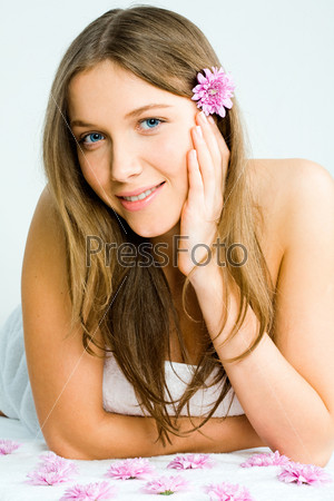 Portrait of a beautiful young woman in towel lying on the massage table