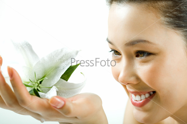 Closeup of beautiful smiling girl looking at fresh white lily in her hand