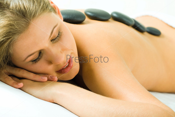 Closeup of woman's face with closed eyes and her back with spa stones on it