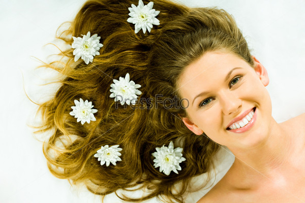 Portrait of a happy fresh girl with flowers in her hair looking at camera with smile