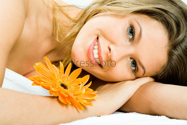 Closeup of beautiful woman's face lying with orange flower on her hand