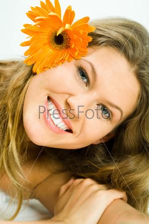 Молодая девушка с цветком в волосах смотрит в камеру