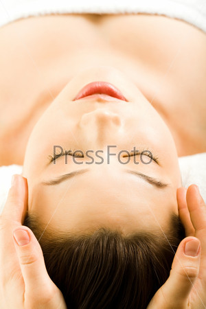 Image of pretty young woman getting a facial massage
