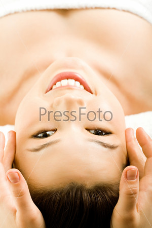 Vertical image of beautiful girl smiling and looking at camera while a facial massage