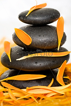 Image of pile of black spa stones with orange petals
