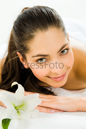 Portrait of a young attractive woman lying in the spa salon and looking at camera