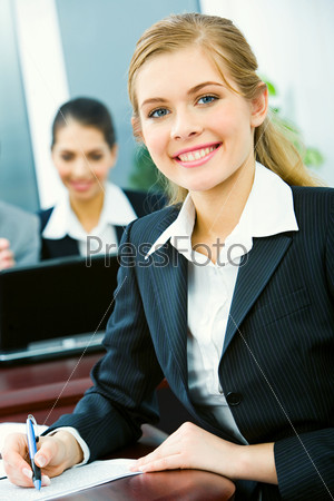 Portrait of pretty professional sitting at the table and holding pen