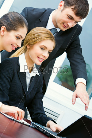 Image of business man pointing to laptop with two women near by