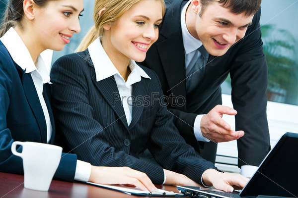 Portrait of business team looking at the laptop at meeting