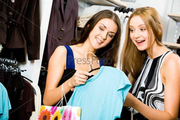 Portrait of young girls in the department store holding fashionable T-shirt