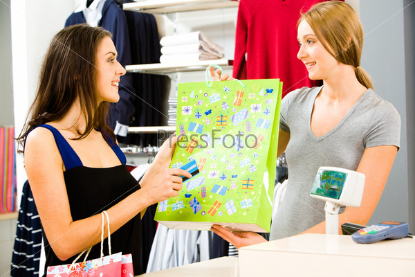 Portrait of a shop assistant holding shopping bag and a pretty girl with credit card