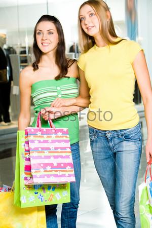 Две молодые женщины держат сумки и смотрят на что-то
