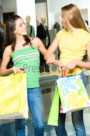 Две женщины разговаривают в торговом центре