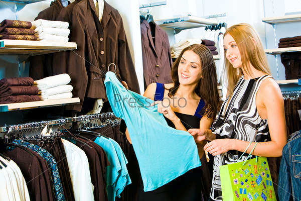 Photo of two girls in the clothing store holding a blue dress and looking at it with smiles