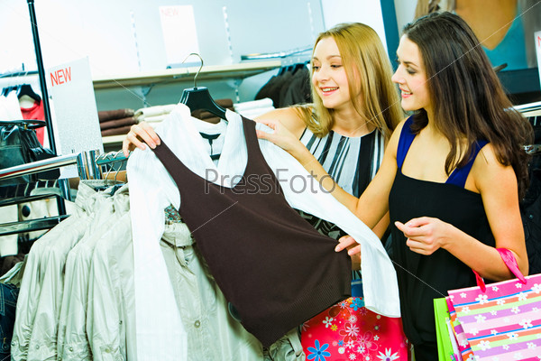 Тwo young smiling ladies in the clothes department looking at fashionable shirt