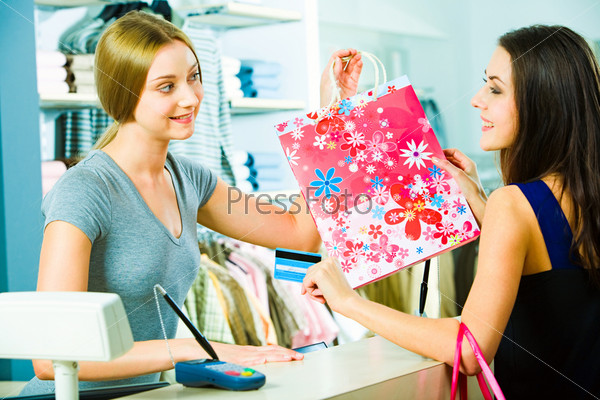 Photo of a friendly salesperson giving shopping bag to pretty customer in the mall