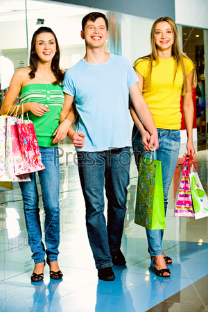 Photo of three happy teenagers with shopping bags in hands looking at something