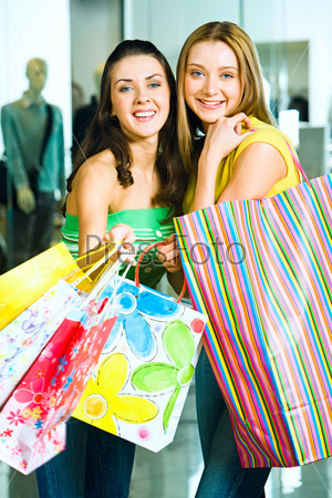 Vertical image of two pretty friends with shopping bags looking at camera with smiles