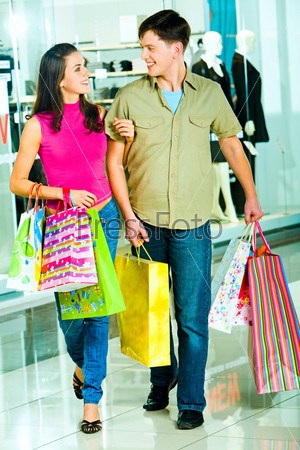 Photo of a young modern couple going shopping in the shopping mall carrying bags