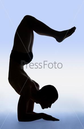 Молодой человек выполняет упражнение из йоги