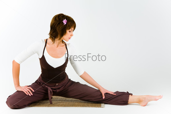Photo of young girl in workout clothes sitting and doing stretching