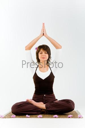 Вертикальное фото женщины, сидящей на коврике и выполняющей йогу