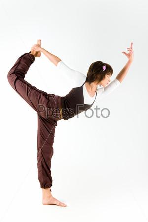 Красивая девушка стоит на одной ноге и держит вторую своей рукой