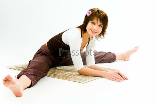 Photo of a sporty girl sitting on a rug with her legs apart and arms in front