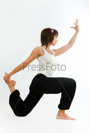 Photo of woman standing on one knee and holding one of her legs behind her back