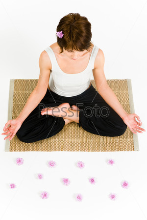 View from above of pretty woman sitting on the floor and doing yoga exercise