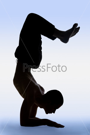 Young man doing an yoga on a blue background