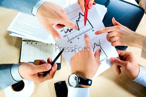 Руки, указывающие на документ, на рабочем месте