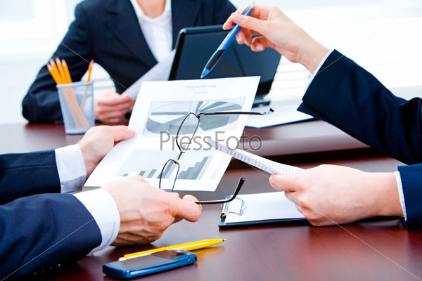 Closeup of business partners' hands holding documents over table during teamwork