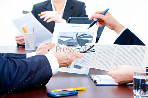 Image of human hands holding the papers and pens