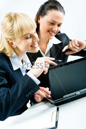 Vertical photo of two pretty businesswomen sitting at laptop and looking at its screen