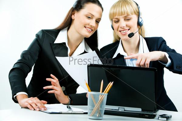 Уверенные профессионалы сидят и обсуждают работу на компьютере