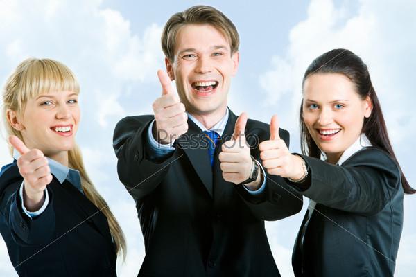 Счастливые деловые партнеры держат большие пальцы вверх на фоне неба